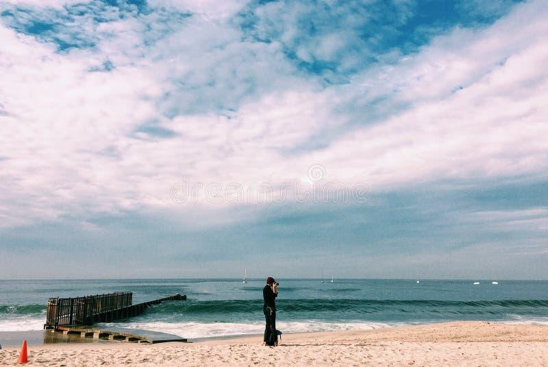 Персона в черной верхней части стоя на Seashore под белыми облаками стоковые фото
