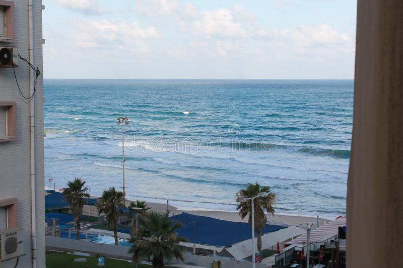 Seashore at Bat Yam, Israel. Waves on the blue stormy sea. Mediterranean coastline. Travelling picture. View from the hotel room between two buildings stock photo