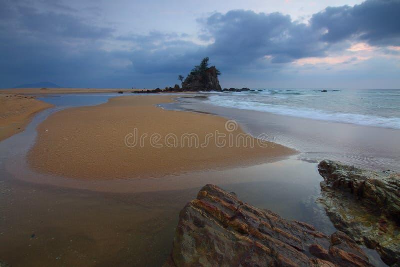 Волна моря разбивая на Seashore с взглядом горной породы с деревьями na górze его под серыми облаками и белым небом стоковые изображения rf