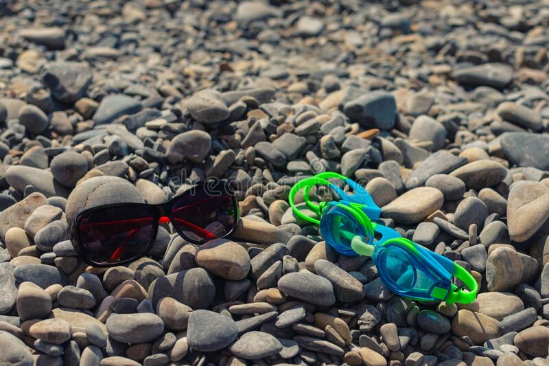 On the seashore, ochki for swimming and ochki goggles from sunlight lie on the stones. Concept of relaxing on a pebble beach on a sunny day. Sea pebbles at the stock photos