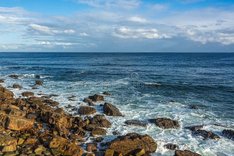 Seashore with rocks, waves,deep blue waters, blue skies with whi. Seashore with rocks, waves crawling gently tonto the rocks no the shore forming white foam stock image