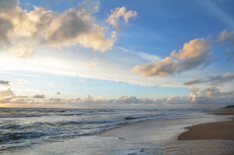 Seashore sky orange and blue tones clouds and sea waves sand beach with beautiful nature bright sunset royalty free stock photography