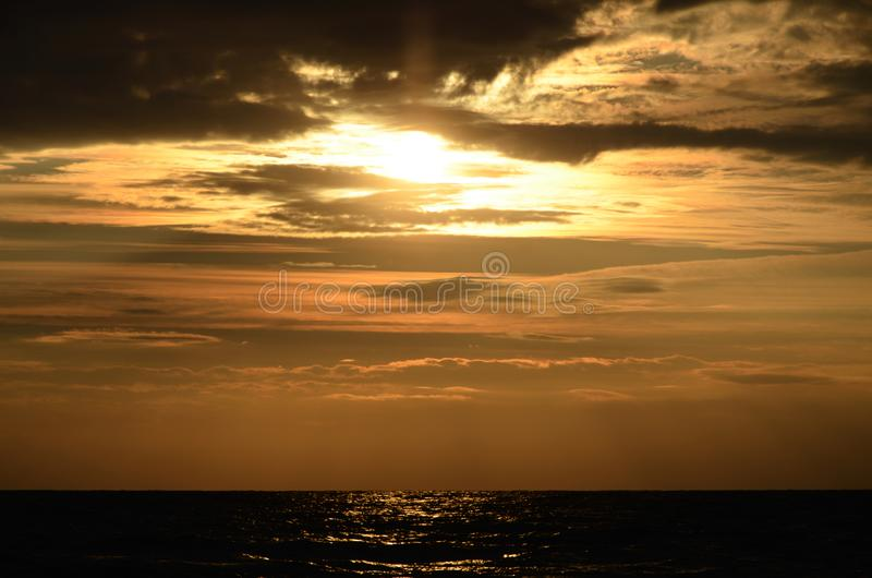 Seashore sky orange tones clouds and sea waves beautiful nature bright sunset dark water royalty free stock images