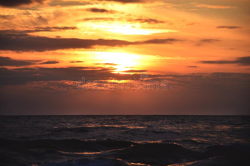 Seashore sky orange tones clouds and sea waves beautiful nature bright sunset dark water stock image
