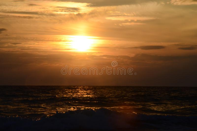 Seashore sky orange tones clouds and sea waves beautiful nature bright sunset dark water royalty free stock photo