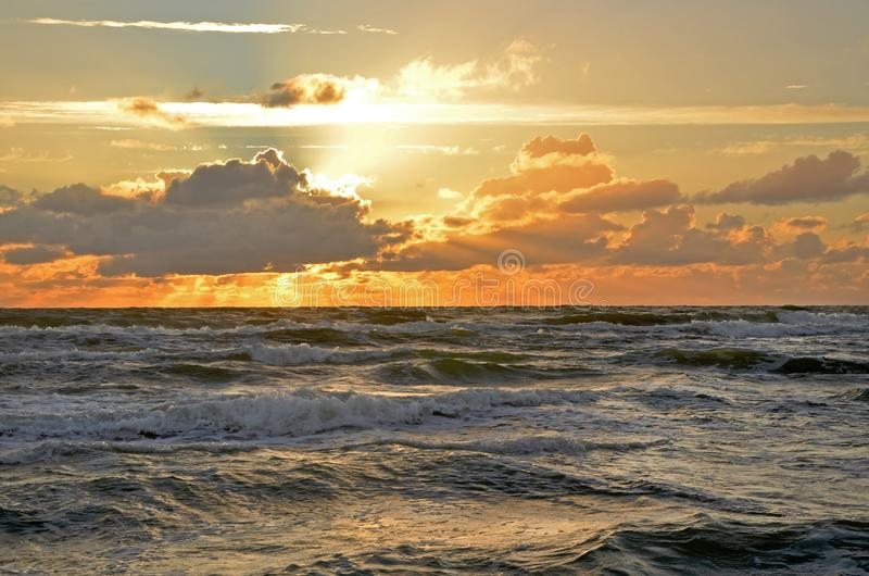 Seashore sky orange tones clouds and sea waves beautiful nature bright sunset dark water royalty free stock photos