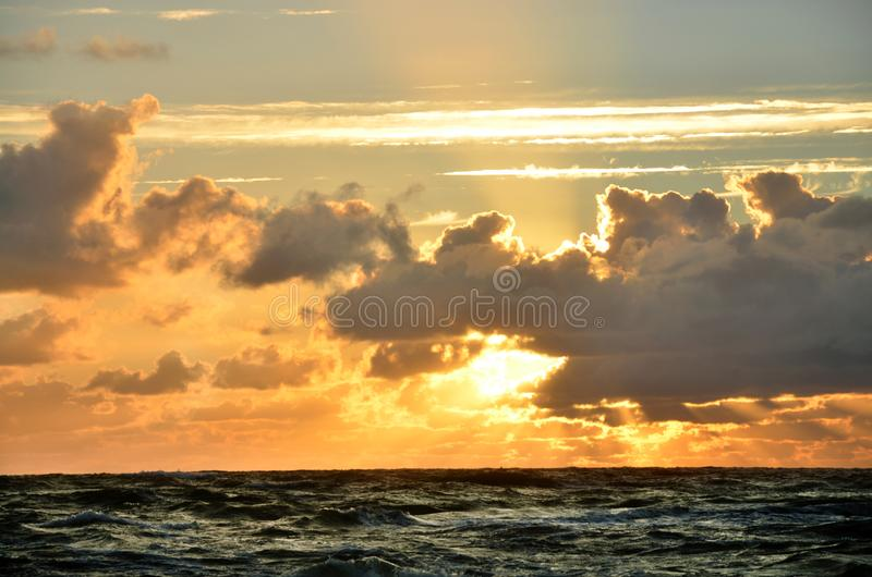Seashore sky orange tones clouds and sea waves beautiful nature bright sunset dark water stock photography