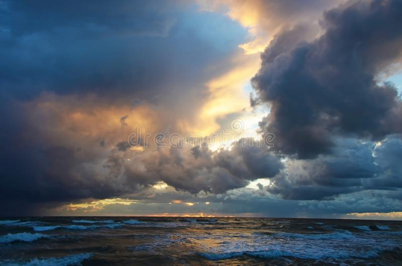 Seashore sky orange tones heavy clouds and sea waves beautiful nature bright sunset dark water royalty free stock photography