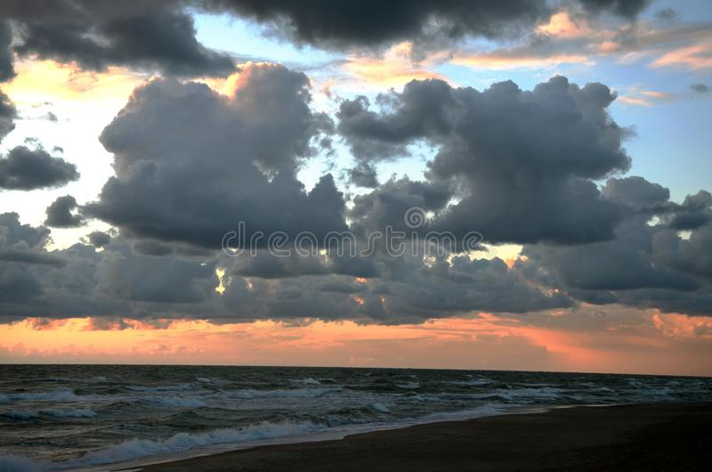 Seashore sky orange tones heavy clouds and sea waves beautiful nature bright sunset dark water stock photos