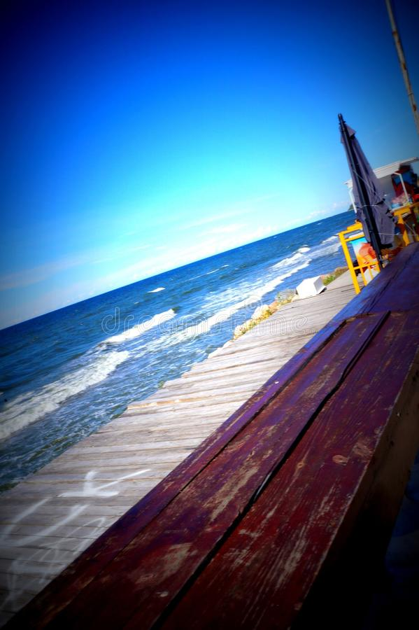 Seashore-view from the boardwalk to the beautiful sea, the sun, the sky. stock photography