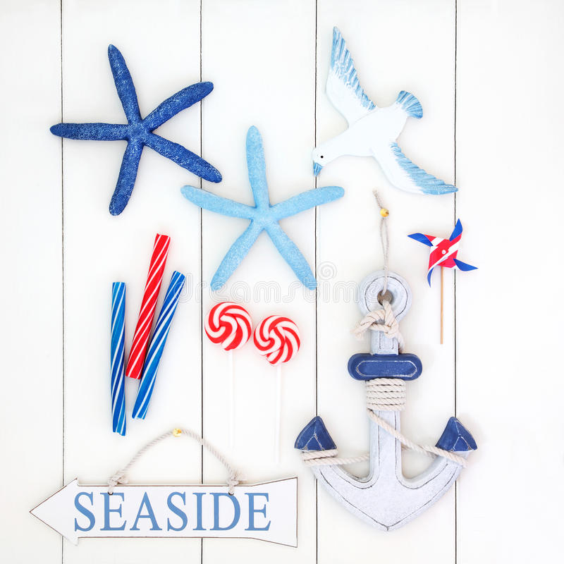 Seaside Abstract. Abstract collage with seaside sign, decorative starfish, anchor, seagull, toy windmill and candy striped rock over white wooden background royalty free stock image
