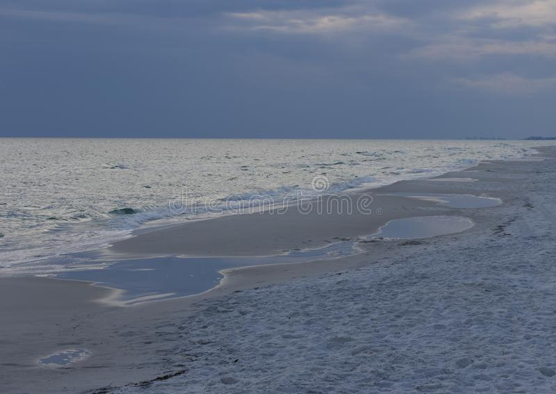 Seaside at Dusk with Approaching Storm. A long stretch of desolate beach, in colors of blue, extends to the horizon as an approaching storm rolls in, clouding royalty free stock image