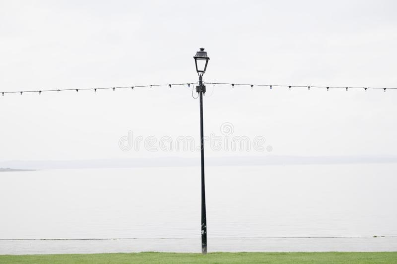 Seaside empty due to wet British summer during rain lonely light line and lamp post stock photos