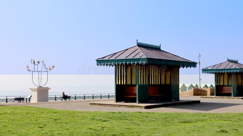 Seaside iconic shelters at Hove. Hove Promenade with iconic seaside shelters , beach huts and an ultramodern sculpture on a pedestal royalty free stock images