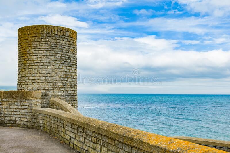 Seaside landscape with brick wall and tower. stock photos