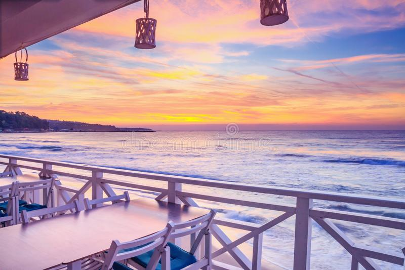 Seaside landscape - the cafe on the embankment with views of the sunrise over the sea stock photo