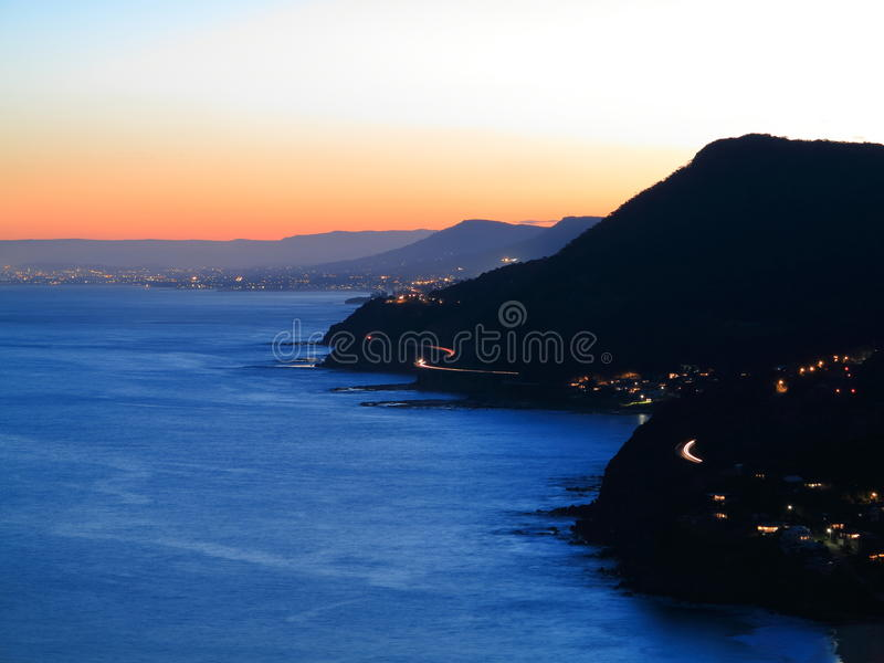 Scenic coastline at sunset Australian landscape. The silhouetted hills and lighted villages at the popular Lawrence Hargrave Drive by dusk. View from Bald Hill royalty free stock images