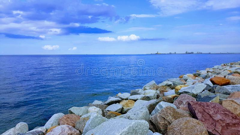 Seaside landscape with ships on the horizon and rocks in the foreground. A seaside landscape with blue sky with clouds and blue water surface. Ships on the royalty free stock photo