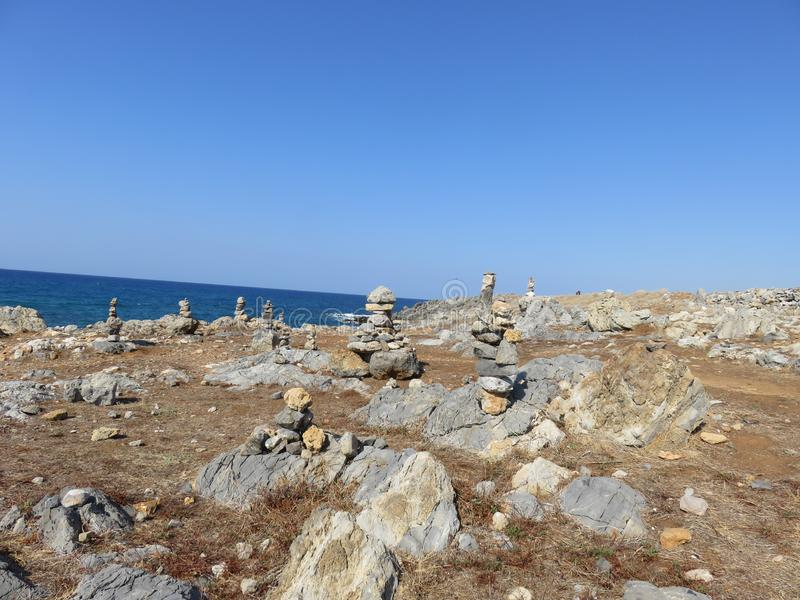 Seaside with a multitude of hand-made stone pyramids stock photos