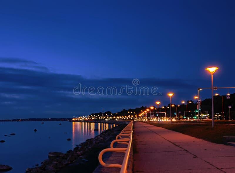 Seaside promenade at night ligt bluurring water reflection neon   Street lamp panorama Tallinn Baltic sea  Nigh modern cit stock photo