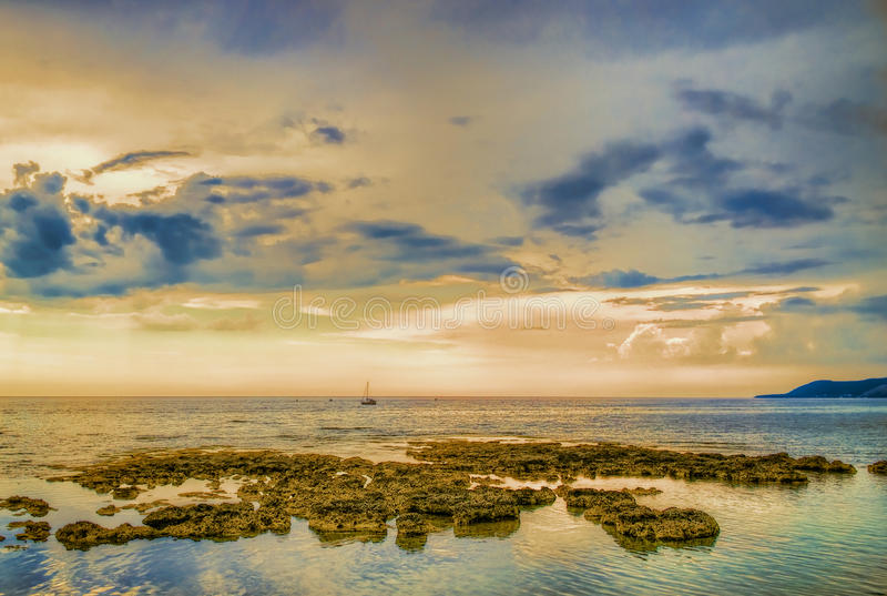 Seaside with sailboat and rocks at dusk stock image