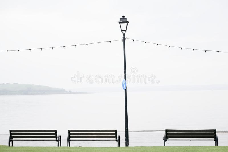 Seaside seats benches empty due to wet British summer during rain stock images