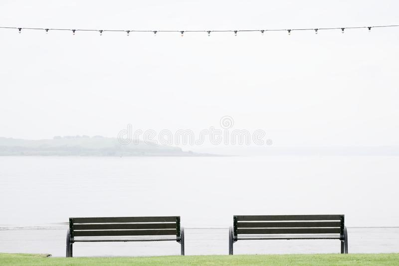 Seaside seats benches empty due to wet British summer during rain stock photography