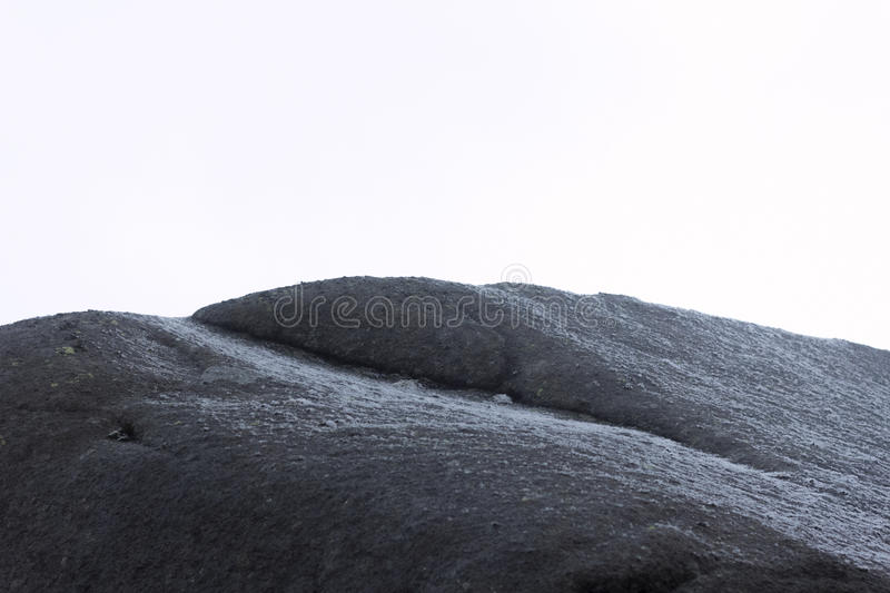 Seaside Stone. A rough but still softly shaped rock surface moistened by salty seawater. Clear daylight is bringing structured gloss. Taken on Lofoten Archipel stock photography