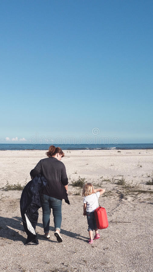 Seaside trip. Mother and daughter camping on the beach stock photos