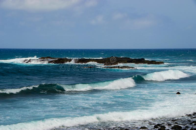 Seaside view on the rocky beach with big waves and blue sky stock photography