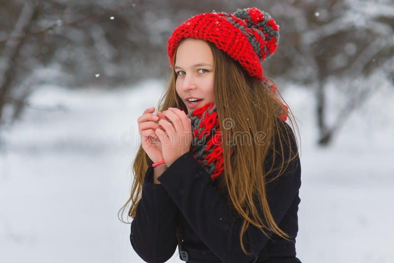 Season christmas or holidays and people concept - smiling young girl in winter clothes outdoor stock photo