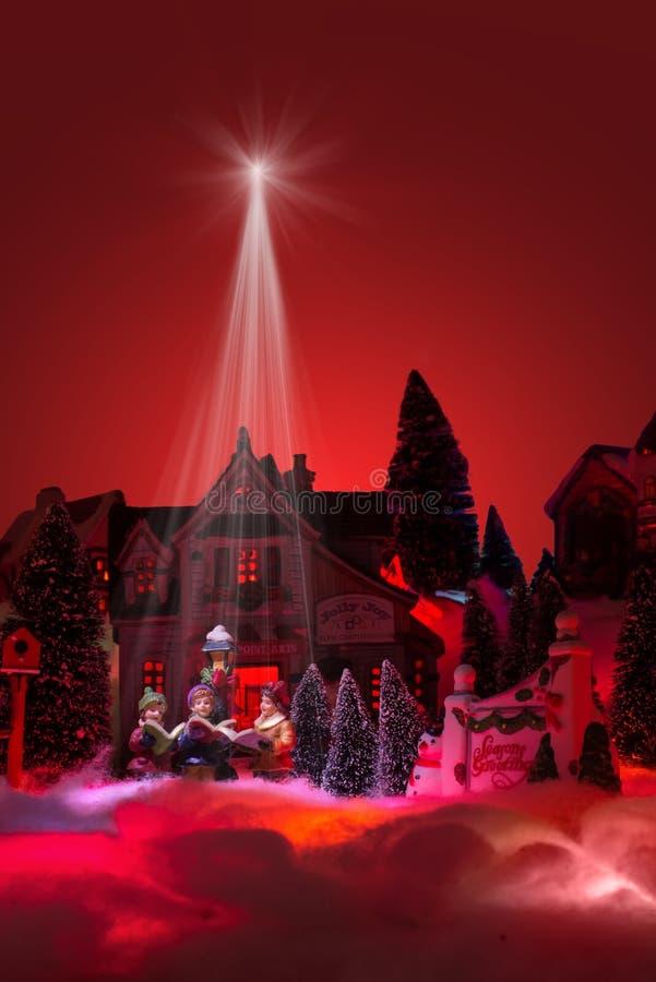 Season greeting with lights from star of bethlehem shines on gospel choir kids. Christmas miniature scenery royalty free stock photo