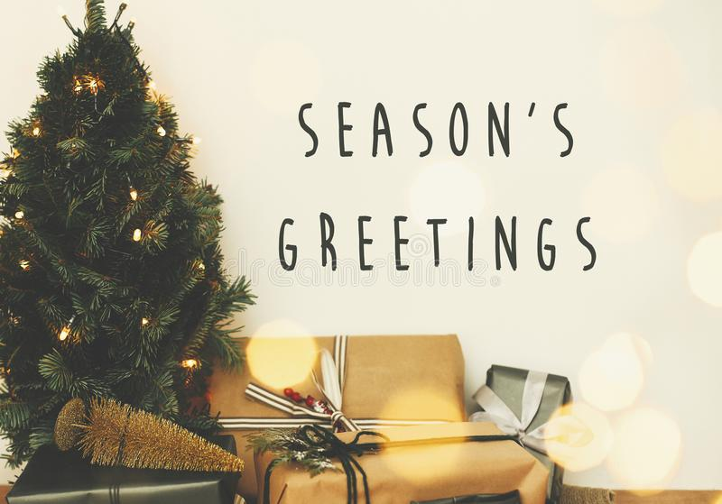 Season`s greetings text sign on christmas tree in golden lights bokeh with festive stylish gifts in white room. Seasons greeting. Card stock photos