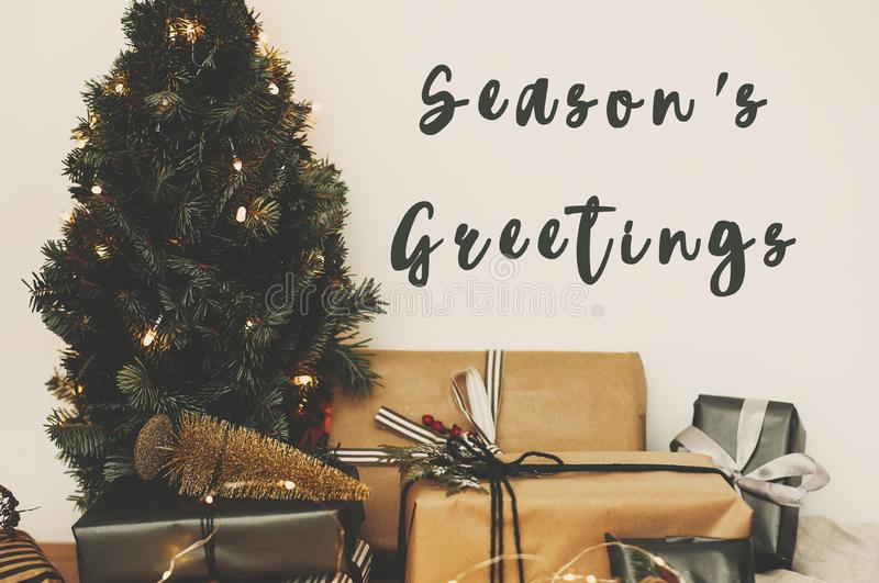 Season`s greetings text sign on christmas tree in golden lights bokeh with festive stylish gifts in white room. Seasons greeting. Card stock photo