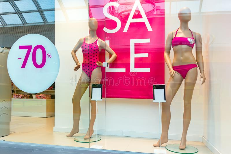 Season sale, black friday and shopping concept. Women`s clothing store showcase. Two woman mannequins in red swimsuits. Sale sign royalty free stock images