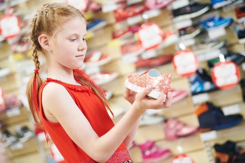 Season sale. Little girl shopping walking shoe. Girl choosing footwear during shopping at garments apparel shoe shop. Season sale stock photo