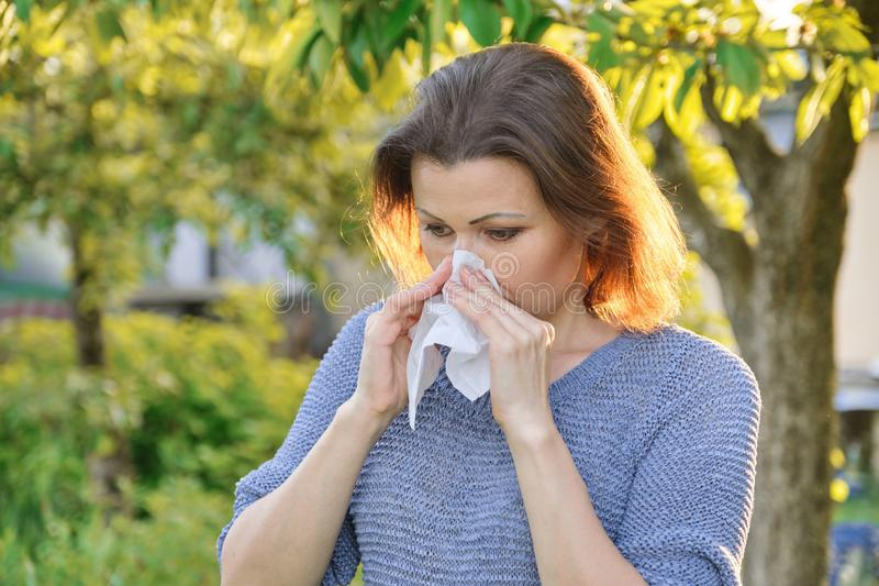 Seasonal allergies, woman with nasal wipe, sneezing, wiping nose outdoor royalty free stock image