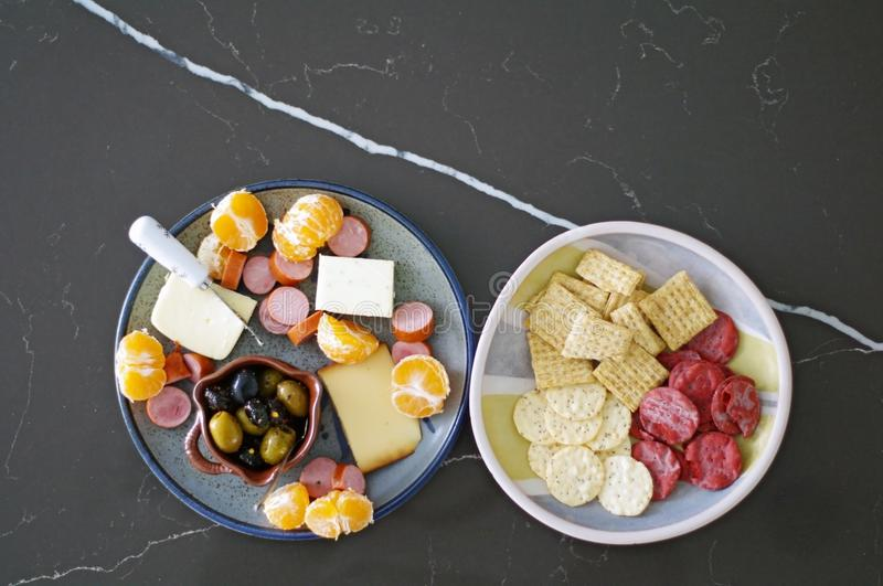 Seasonal appetizer platter with olives, cheese, meat and oranges stock photography