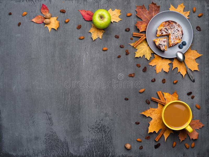 Seasonal autumn background. Frame of colorful maple leaves and a cup of hot drink, coffee, latte or cappuccino, nutmeg. Cake, apple and cinnamon over grey royalty free stock photography