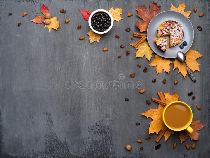 Seasonal autumn background. Frame of colorful maple leaves and a cup of hot drink, coffee, latte or cappuccino, nutmeg. Cake, black currant and cinnamon over royalty free stock photo