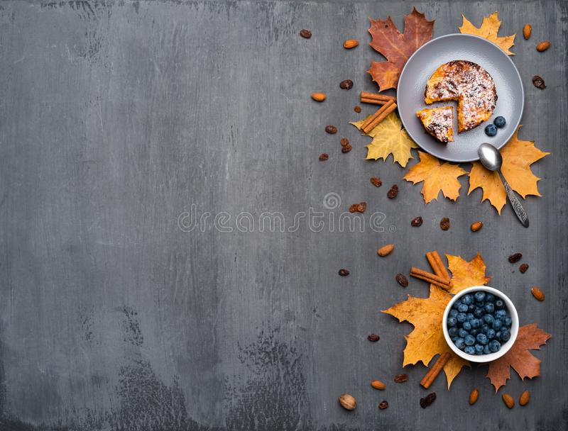 Seasonal autumn background. Frame of colorful maple leaves and a cup of hot drink, coffee, latte or cappuccino, nutmeg. Cake, blueberries and cinnamon over royalty free stock photography