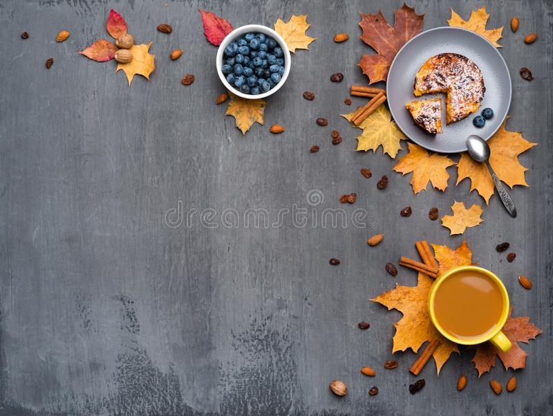 Seasonal autumn background. Frame of colorful maple leaves and a cup of hot drink, coffee, latte or cappuccino, nutmeg. Cake, blueberries and cinnamon over stock images