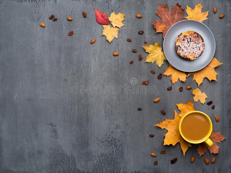 Seasonal autumn background. Frame of colorful maple leaves and a cup of hot drink, coffee, latte or cappuccino, nutmeg. Cake and cinnamon over grey texture royalty free stock photos