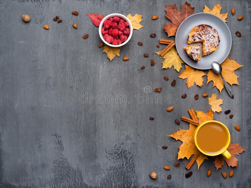 Seasonal autumn background. Frame of colorful maple leaves and a cup of hot drink, coffee, latte or cappuccino, nutmeg. Cake, raspberries and cinnamon over stock image