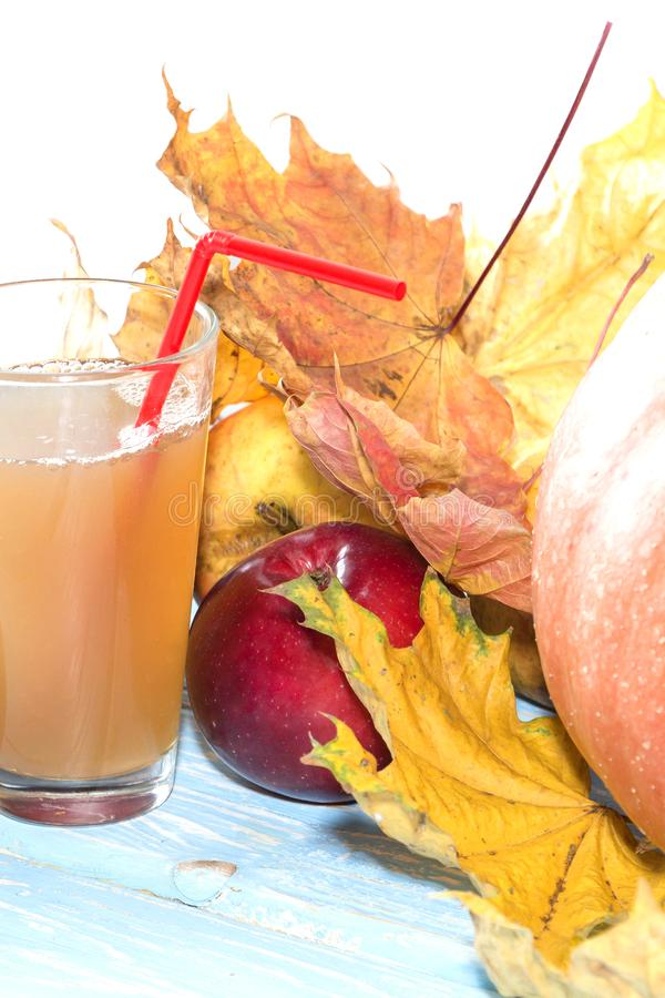 Seasonal autumn. Pumpkin fresh juice drink cocktail on a white table with fall maple leaves. royalty free stock images