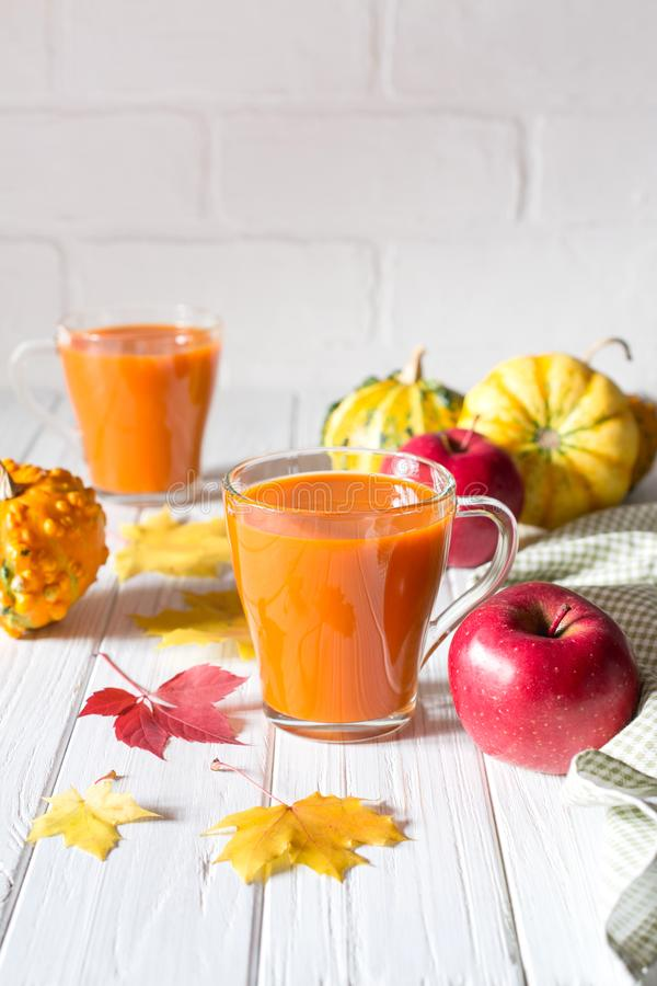 Seasonal autumn thanksgiving concept. Pumpkin fresh juice drink cocktail on a white table with fall maple leaves. stock photography
