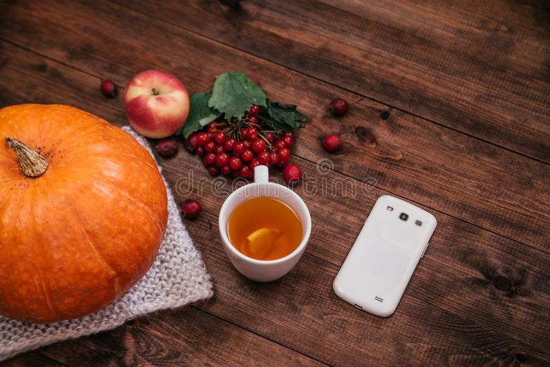 Autumn workplace, pumpkin, apples and book, phone on wooden table royalty free stock image