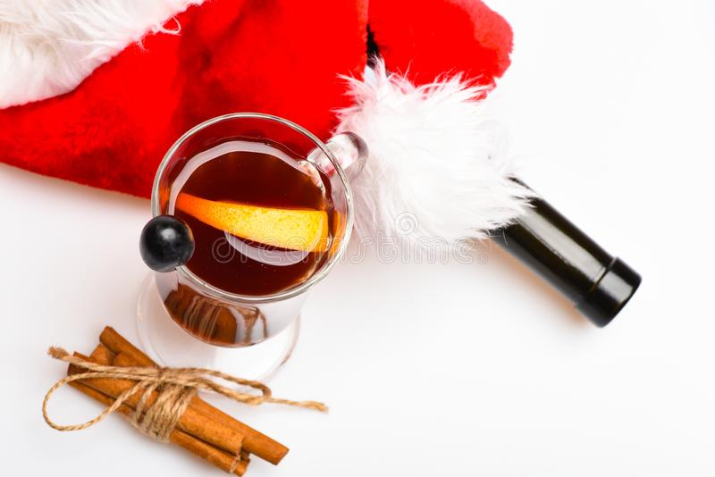 Seasonal beverage concept. Glass with mulled wine or hot drink with grape cinnamon near Santas hat, white background. Close up. Glass with mulled wine with royalty free stock photos