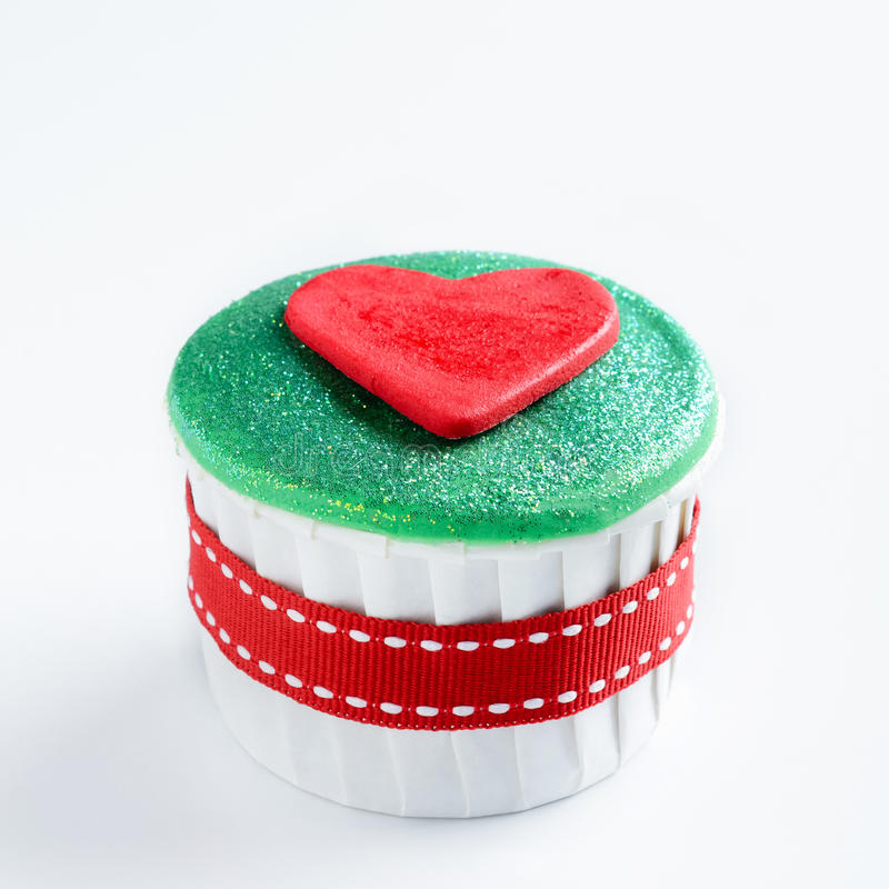 Seasonal christmas cupcake. Christmas cupcake in traditional red green colours with heart decorative element stock image
