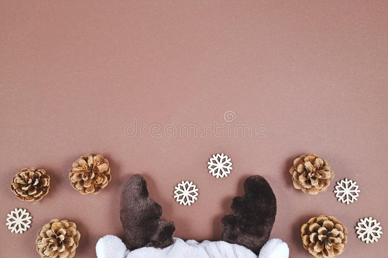 Seasonal Christmas flat lay background with cute plush reindeer antlers with pine cones and wooden snowflakes at bottom and empty royalty free stock photos